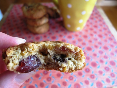 Cherry, chocolate, cornflake and coconut cookies with a bite taken out of it.