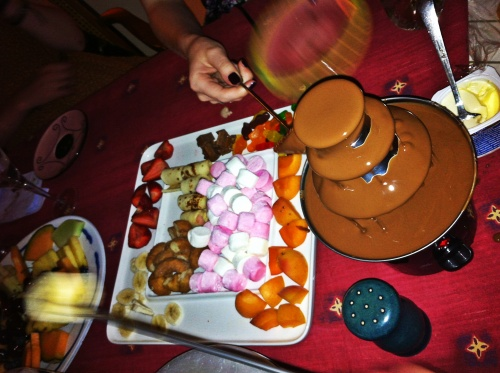 Chocolate fondue fountain on a table with fruit and sweets