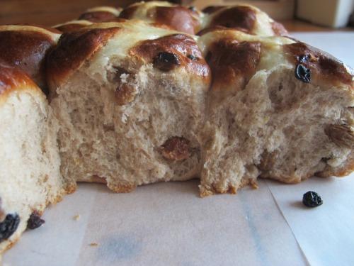 Close up of hot cross bun with sultanas