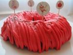 A round cake with red icing piped in lines with silver balls