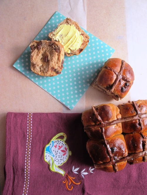 Chocolate chip hot cross buns with one ripped in half