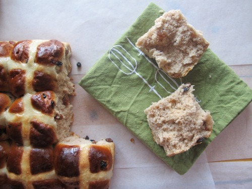 Loaf of hot cross buns with one ripped off and ripped in half